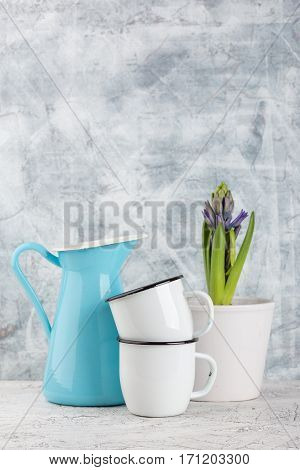 Two white enamel mugs blue jug and blossoming flower hyacinth in pot on light background