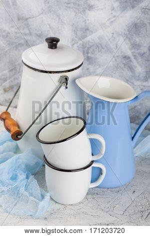 Two white enamel mug jug blue and white can on light background