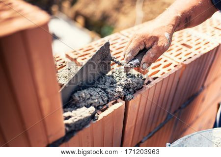 Industrial Details - Construction Bricklayer Worker Building Walls With Bricks, Mortar And Putty Kni