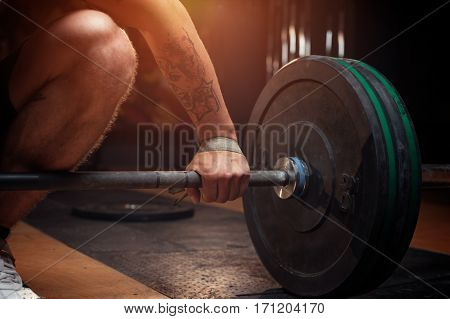 Cropped shot of young man preparing for barbell training in gym. Weightlifting, power lifting equipment. Sports, fitness - healthy lifestyle concept.
