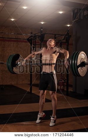 Strong muscular man lifting barbell in gym. Weightlifting, power lifting workout. Sports, fitness - healthy lifestyle concept