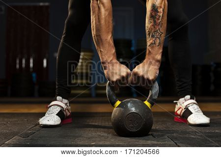 Cropped shot of male hands holding kettlebell. Muscular man doing weightlifting exercises. Sports, fitness concept.