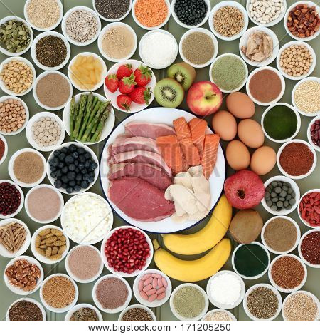 Large health food selection for body builders with meat, salmon, dairy, fruit, nuts, pulses, seeds, cereals  and supplement powders forming a background.