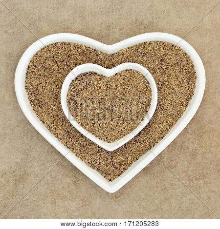 Teff grain health and super food in heart shaped porcelain bowl on hemp paper background.