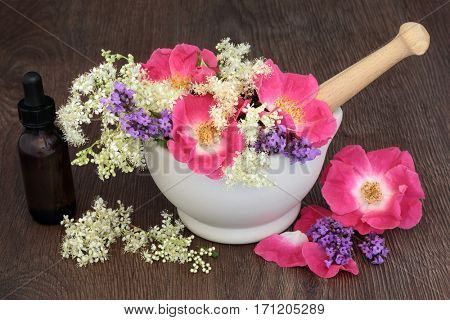 Elderflower, rose and lavender herb flowers used in natural alternative herbal medicine in a mortar with pestle and aromatherapy essential oil bottle.