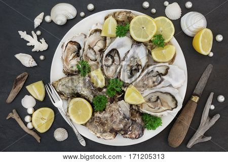 Oysters with old oyster knife and silver fork, lemon fruit, parsley herb, pearls, shells and driftwood on a slate.