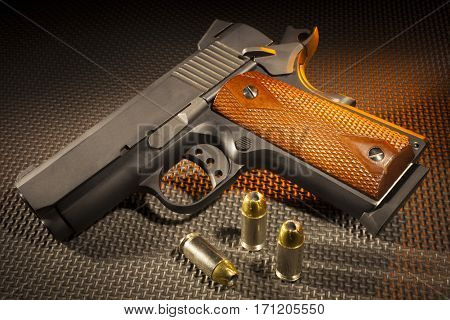 Semi automatic handgun with three bullets on a rubber mat