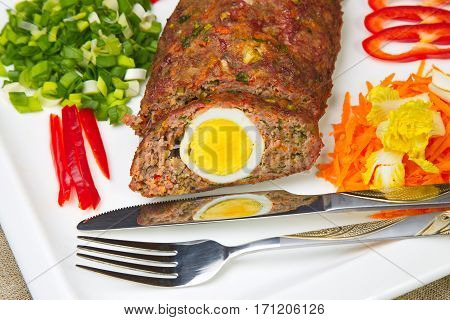 Meatloaf with egg sliced on a plate.