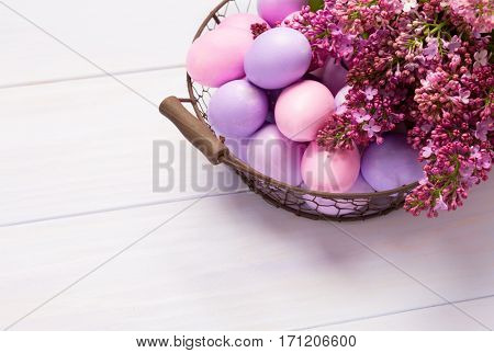 Easter eggs and  lilac  flowers on   wooden table. View from above.