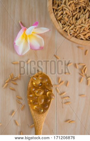rice bran oil capsules and paddy Natural Supplement on wooden background.
