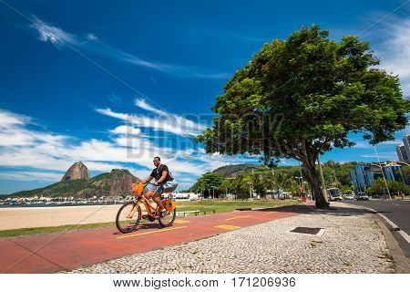 Rio de Janeiro, Brazil - January 27, 2017: Unidentified young man is riding a bicycle on a cycling path in Botafogo beach.