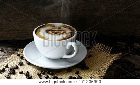 Big hearts coffee. Cappuccino coffee. A cup of latte, cappuccino or espresso coffee with milk put on a wood table with dark roasting coffee beans. Drawing the foam milk on top.
