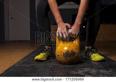 Young female athlete doing exercise with kettlebell in gym. Weightlifting, power lifting workout. Sports, fitness concept.