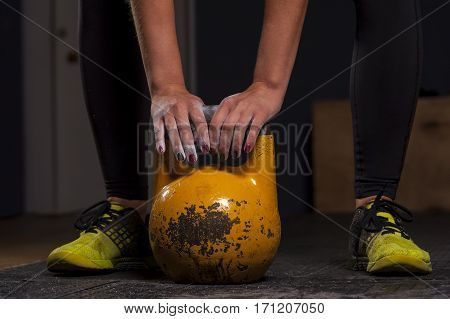 Cropped shot of female athlete doing exercises with kettlebell. Weightlifting, power lifting equipment. Sports, fitness concept.