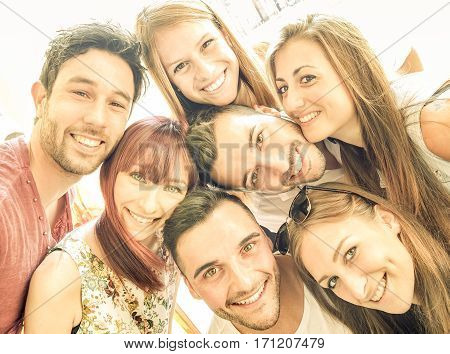 Happy best friends taking selfie outdoors with spring time backlighting - Friendship and happiness concept with young people having fun together - Warm vintage filter with bright sunshine color tones