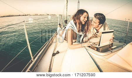 Young couple in love on sail boat having fun with tablet - Happy luxury lifestyle on yacht sailboat - Technology interaction with satellite wifi connection - Retro contrasted filter