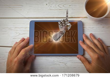 Composite image of robotic hand pointing against hands using tablet on desk 3d