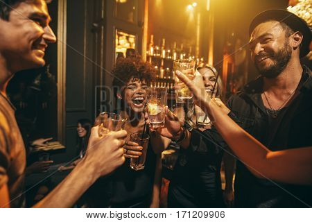 Shot of young men and women enjoying a party. Group of friends having drinks at nightclub.