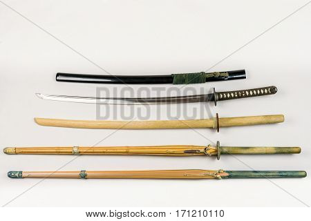 A collection of weapons for training, equipment for Japanese sport Iaido and Kendo. Wood, bamboo and steel sword arranged and displayed.