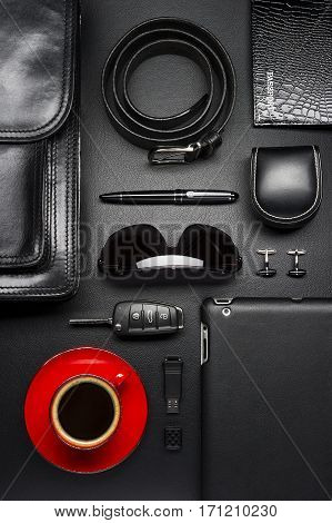 Man accessories in business style with cup of coffee, gadgets, car key, cufflinks, eyewear, briefcase and other luxury businessman attributes on leather black background, fashion industry