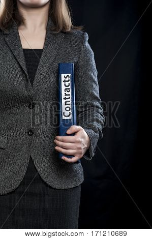 Woman manager with blue folder with inscription Contracts.