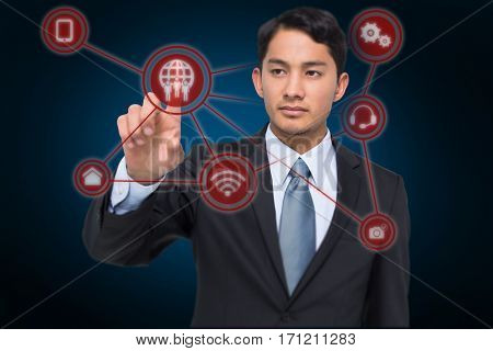 Stern asian businessman pointing against blue background with vignette