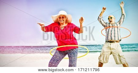 Senior couple doing hula hoop on beach