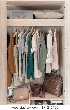 Clothes Hanging On Rail In Wooden Wardorbe