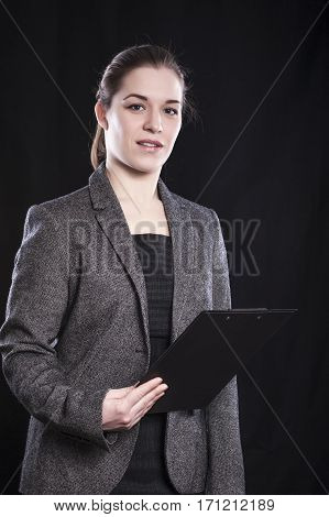 Confident woman manager with clipboard on black background.