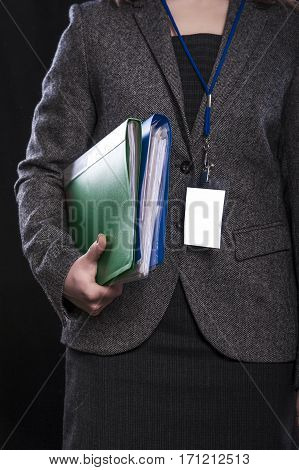 Office employee with documents in her hands on black background.