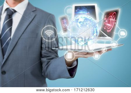 Midsection of businessman holding tablet computer against blue background 3d