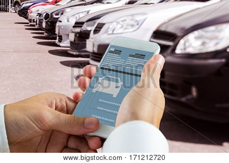 hand holding smartphone against view of row new car