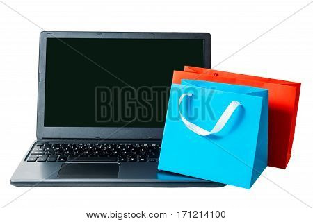 Shopping bags and open laptop isolated on white background. Online shopping concept.