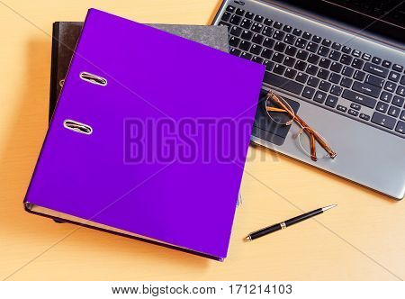 Folders with laptop computer  and pen on desk