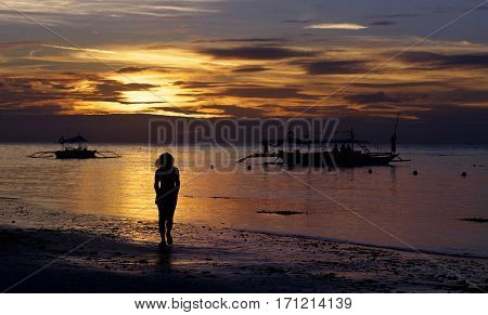 One alone woman going on coastline in colorful dramatic sunset golden hours with golden sky and boats background, one woman on sunset, golden sunset hours in tropics, amazing sunset