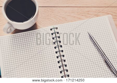 Notebook diary and espresso coffee cup closeup. Office or student's devices on modern wooden desk. Working table top view. Education, writing and studying background with copy space on paper sheet