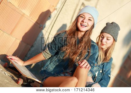 Two beautiful and young girlfriends having fun with a skateboard