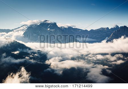 Creamy fog covered the famous glacier Marmolada in evening light. Dramatic and gorgeous scene. Location place Val di Fassa valley, passo Sella, Dolomiti, South Tyrol. Italy, Europe. Beauty world.