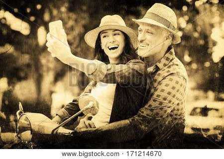 Grey background against happy couple taking selfie on moped