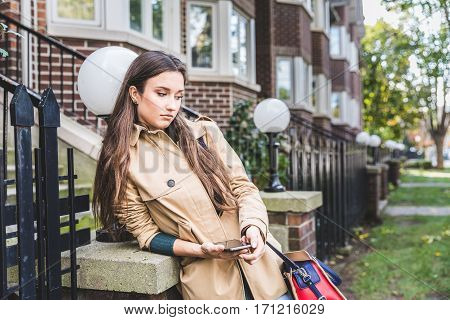 Sad Woman With A Smart Phone In A Residential Area