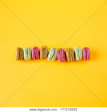 pink brown orange and green macarons on yellow background