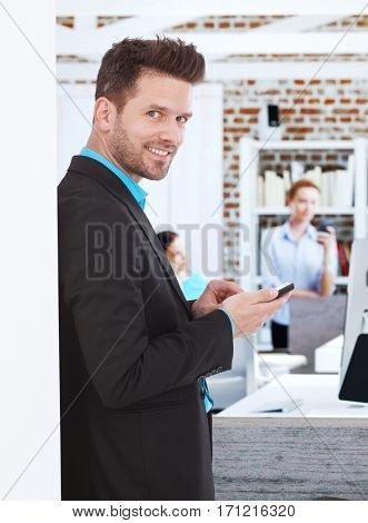 Happy businessman standing by wall, using mobilephone.