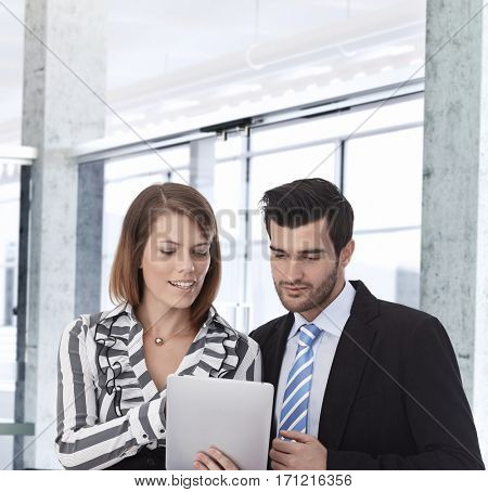 Businesspeople working together, using tablet computer.