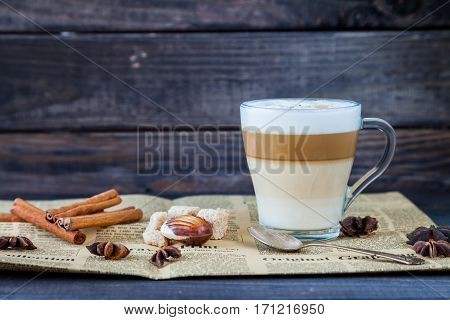 Hot latte macchiato coffee with tasty foam in tall clear glass on dark wooden table serving with cinnamon, cane sugar, retro newspaper and roasted coffee beans. Breakfast time. Low key photo.