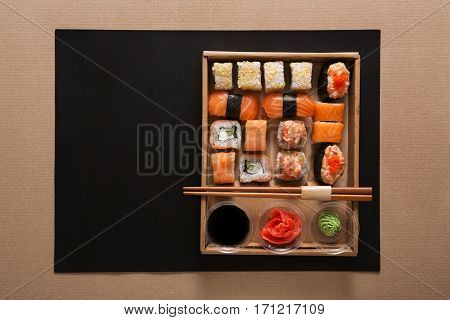 Japanese food restaurant take away in craft carton, sushi maki gunkan roll plate or platter set. Chopsticks, ginger, soy sauce, wasabi. Meals in delivery box. Top view.
