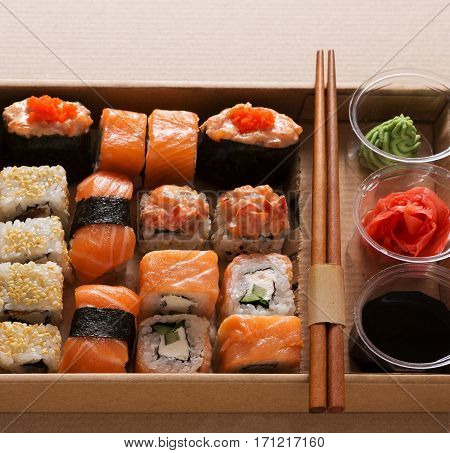 Japanese food restaurant take away in craft carton, salmon sushi, gunkan and rolls plate or platter set. Chopsticks, ginger, soy sauce, wasabi. Meals in delivery box, closeup