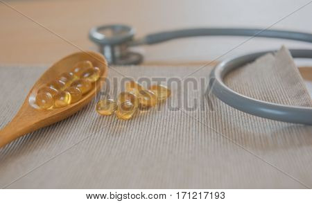 oil gel capsules and stethoscope . Natural Supplement for vascular health on wooden background.
