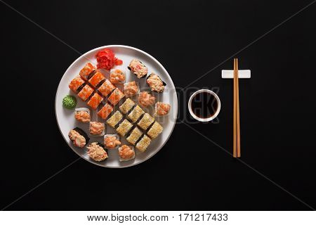 Japanese food restaurant, california salmon rolls, gunkans and sushi platter. Set with chopsticks and soy sauce. Top view on black background