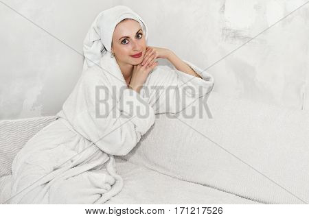 Beautiful girl sitting on the sofa in a fluffy Bathrobe in a room with no Wallpaper on the walls needed to be repaired. White background, high key. Plenty of space for text.