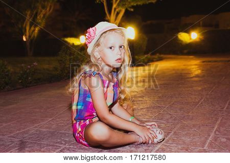 Portrait of cute little girl sitting on the ground at the evening time. Active summer vacation on the beach.